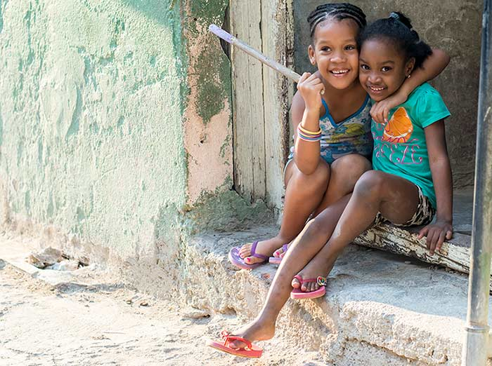 Two Cuban girls play on the street after school.