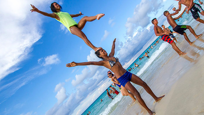 Cuban female acrobats on beach.